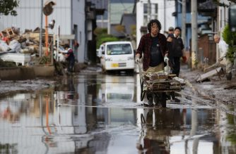 A man removes muddy items at a flood-affected area in Nagano on October 15, 2019, after Typhoon Hagibis hit Japan on October 12 unleashing high winds, torrential rain and triggered landslides and catastrophic flooding. - Rescuers in Japan worked into a third day in an increasingly desperate search for survivors of a powerful typhoon that killed nearly 70 people and caused widespread destruction. (Photo by STR / JIJI PRESS / AFP) / Japan OUT