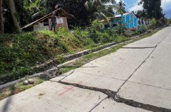 A resident stands near a huge crack in a cemented road caused by a 6.4 magnitude earthquake the night before, in the town of Magsaysay in Davao del Sur on the southern Philippine island of Mindanao on October 17, 2019. - Three children were among four people killed after the powerful earthquake hit the southern Philippines, authorities said on October 17. (Photo by Manman Dejeto / AFP)
