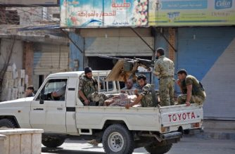Turkish-backed Syrian fighters ride in the back of a pick up truck in the Syrian border town of Tal Abyad on October 18, 2019, after a ceasefire was announced the previous day. - Deadly Turkish air strikes shattered an hours-old US-brokered deal to stop Ankara's military offensive against Kurdish forces in northeastern Syria. The ceasefire announced late Thursday was meant to provide a pause for the evacuation of Kurdish fighters from the battleground border town of Ras al-Ain and other areas Turkey wants to control along its border with Syria. (Photo by Bakr ALKASEM / AFP)