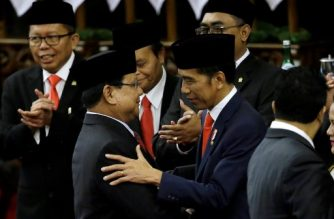 Indonesian President Joko Widodo (R) shakes hands with Chairman of Gerindra Party Prabowo Subianto after Jokowi was sworn in for a second term as president at the parliament building in Jakarta on October 20, 2019. - Indonesia's President Joko Widodo was sworn in for a second term on October 20, as helicopters flew overhead and troops kept watch in the capital Jakarta -- days after Islamist militants tried to assassinate his top security minister. (Photo by Achmad Ibrahim / POOL / AFP)