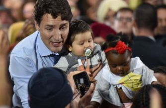 "Leader of the Liberal Party of Canada, Prime Minister, Justin Trudeau, poses for photos with babies in a crowd of supporters during a ""Team Trudeau 2019"" Rally at the Woodward's Atrium in Vancouver B.C. on October 20, 2019. (Photo by Don MacKinnon / AFP)"