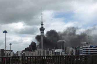 Thick smoke blows from a construction site at the SkyCity convention centre in Auckland on October 22, 2019. - A huge fire at a construction site sent clouds of acrid black smoke billowing over Auckland forcing large parts of the downtown area to be cordoned off as firefighters battled the blaze. (Photo by Greg Bowker / AFP)
