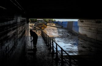 A worker cleans a flooded road under a bridge close to the sea, in Arenys de Mar, Catalonia, on October 23, 2019, following torrential rains in northeastern Spain. - Authorities said heavy overnight rainfall in the northeastern region of Catalonia caused power cuts that affected nearly 25,000 people while floods and landslides forced the closure of over 40 roads. (Photo by Josep LAGO / AFP)