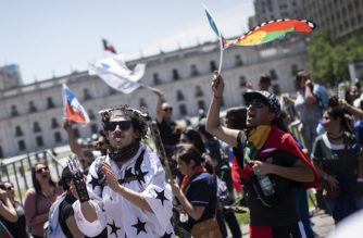 """People demonstrate against the government economic policies in front of La Moneda presidential palace in Santiago, on October 30, 2019. - Chile pulled out of hosting two major international summits Wednesday as it struggled to restore order amid clashes between protestors and security forces that have left at least 20 dead. President Sebastian Pinera said """"common sense"""" had dictated the decision to withdraw from the Asia Pacific Economic Cooperation summit and the Cop 25 climate change conference. (Photo by Pedro Ugarte / AFP)"""