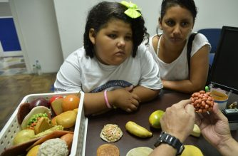 "Colombian 8-year old Dana Garcia (L) listens to a doctor talking about nutrition, in Medellin, Antioquia department, Colombia on February 25, 2015, after she was rescued by members of ""Gorditos de Corazon"" (Chubby at Heart) foundation in Sucre department and then transferred to Medellin city. Garcia, whose ideal weight is 24 kg, is currently 90 kg.   AFP PHOTO / RAUL ARBOLEDA (Photo by RAUL ARBOLEDA / AFP)"
