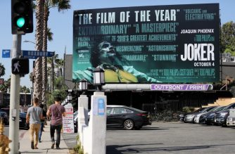 WEST HOLLYWOOD, CALIFORNIA - OCTOBER 03: People walk past a billboard displayed for the new film 'Joker' on October 3, 2019 in West Hollywood, California. Security measures have been tightened in some cities around the film's opening weekend following concerns of potential violence at theaters.   Mario Tama/Getty Images/AFP