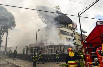 "Firefighters work to extinguish a fire at Ecuadorean TV station Teleamazonas offices in Quito on October 12, 2019, after it was attacked by demonstrators during the 10th day of a protest over a fuel price hike ordered by the government to secure an IMF loan."" (Photo by Martin BERNETTI / AFP)"