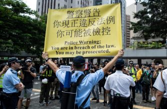 A police officer displays a warning banner during a flash mob rally to show support for pro-democracy protesters at Chater Garden in the Central district in Hong Kong on October 11, 2019. (Photo by Mohd RASFAN / AFP)