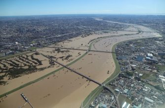 This aerial view shows the swollen Arakawa river in the aftermath of Typhoon Hagibis dividing Tokyo and Saitama prefecture on October 13, 2019. (Photo by STR / JIJI PRESS / AFP)