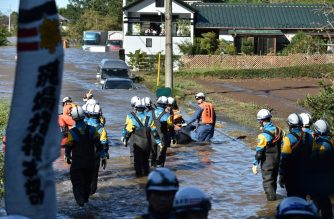 Rescue personnel use a boat to evacuate people and caregivers from the Kawagoe Kings Garden elderly care center in Kawagoe city, Saitama prefecture on October 13, 2019. (Photo by Kazuhiro NOGI / AFP)