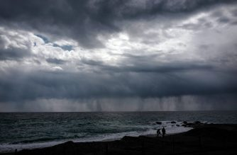 People walk on the beach in front of a curtain of rain on April 14, 2019 in Bordighera in Italy. (Photo by VALERY HACHE / AFP)