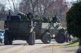 Canadian military vehicles drive near a flooded street in Sainte-Marthe-sur-le-Lac in the suburbs of Montreal, Quebec, Canada, on April 28, 2019. - Ottawa's mayor declared a state of emergency in the Canadian capital on April 25 in anticipation of rising flood waters and heavy rains. (Photo by Sebastien St-Jean / AFP)