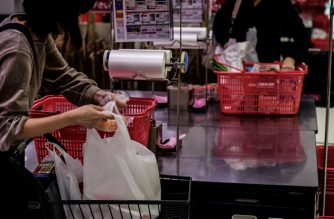 (FILES) In this file photo taken on November 7, 2018, a customer packs her shopping into a plastic bag in a supermarket in Chiba. - Japanese retailers including supermarkets and convenience stores will be required to charge for plastic bags ahead of the Tokyo Olympics, a government panel agreed on November 1, 2019. (Photo by Martin BUREAU / AFP)