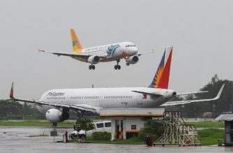 (FILES) This file photo taken on July 17, 2018 shows a Cebu Pacific Airbus A320 (top) preparing to land past a Philippine Airlines aircraft (R) at Manila International Airport. - The Philippines' largest budget airline Cebu Air Inc, commonly referred to as Cebu Pacific, has ordered 16 Airbus planes worth 4.8 billion USD, the carrier said November 4, 2019 as it aims to expand carrying capacity with larger, more fuel-efficient jets. (Photo by TED ALJIBE / AFP)