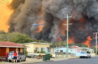 """This handout picture taken and received from Kelly-ann Oosterbeek on November 8, 2019 shows flames from an out of control bushfire seen from a nearby residential area in Harrington, some 335 kilometers northeast of Sydney. - Australian firefighters warned they were in """"uncharted territory"""" as they struggled to contain dozens of out-of-control bushfires across the east of the country on November 8. (Photo by Kelly-ann Oosterbeek / Kelly-ann Oosterbeek / AFP) / RESTRICTED TO EDITORIAL USE - MANDATORY CREDIT """"AFP PHOTO / KELLY-ANN OOSTERBEEK"""" - NO MARKETING NO ADVERTISING CAMPAIGNS - DISTRIBUTED AS A SERVICE TO CLIENTS == NO ARCHIVE"""