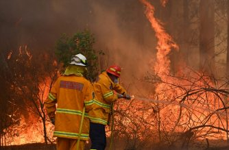 Firefighters tackle a bushfire to save a home in Taree, 350km north of Sydney on November 9, 2019 as they try to contain dozens of out-of-control blazes that are raging in the state of New South Wales. - At least two people have died and 100 homes have been destroyed as an unprecedented number of bushfires tore through eastern Australia. (Photo by PETER PARKS / AFP)
