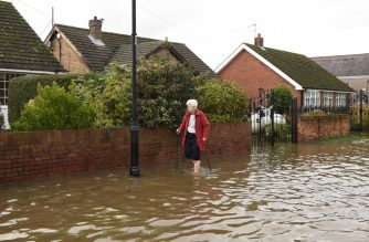 A resident walks along a flooded street in the village of Fishlake near Doncaster, northern England, on November 11, 2019 following heavy rain and the River Don bursting its banks. - Over a month's worth of rain fell on parts of England on November 7, with some people forced to evacuate their homes, including around half the 700 residents of Fishlake, after the River Don burst its banks. (Photo by Oli SCARFF / AFP)