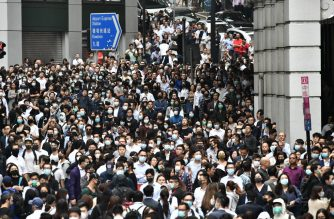 Office workers join pro-democracy protesters during a demonstration in Central in Hong Kong on November 12, 2019 following a day of pro-democracy protests. - A Hong Kong police officer shot at masked protesters -- hitting at least one in the torso -- during clashes broadcast live on Facebook, as the city's rush hour was interrupted by protests. (Photo by Anthony WALLACE / AFP)