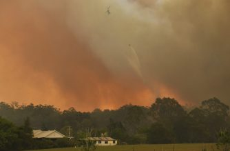 A helicopter drops water on a homestead as bushfires impact on farmland near the small town of Nana Glen, some 600kms north of Sydney on November 12, 2019. - Bushfires reached within kilometres (miles) of Sydney's city centre prompting firefighting planes to spray red retardant over trees and houses in a northern suburb. (Photo by WILLIAM WEST / AFP)