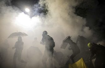 Protesters react amongst tear gas canister during clashes with police at the Chinese University of Hong Kong (CUHK) in Hong Kong on November 12, 2019. - Hong Kong pro-democracy protesters clashed with riot police in the city's upmarket business district and on university campuses on November 12, extending one of the most violent stretches of unrest seen in more than five months of political chaos. (Photo by DALE DE LA REY / AFP)