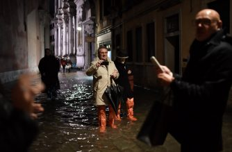 "People wearing waterproof gear walk through a flooded street during an exceptional ""Alta Acqua"" high tide water level on November 12, 2019 in Venice. - Powerful rainstorms hit Italy on November 12, with the worst affected areas in the south and Venice, where there was widespread flooding. Within a cyclone that threatens the country, exceptional high water were rising in Venice, with the sirocco winds blowing northwards from the Adriatic sea against the lagoon's outlets and preventing the water from flowing back into the sea. At 22:40pm the tide reached 183 cm, the second measure in history after the 198 cm of the 1966 flood. (Photo by Marco Bertorello / AFP)"