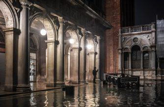 "A man stands by a flooded square during an exceptional ""Alta Acqua"" high tide water level late on November 12, 2019 in Venice. - Powerful rainstorms hit Italy on November 12, with the worst affected areas in the south and Venice, where there was widespread flooding. Within a cyclone that threatens the country, exceptional high water were rising in Venice, with the sirocco winds blowing northwards from the Adriatic sea against the lagoon's outlets and preventing the water from flowing back into the sea. At 22:40pm the tide reached 183 cm, the second measure in history after the 198 cm of the 1966 flood. (Photo by Marco Bertorello / AFP)"
