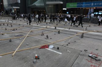 "Protesters and office workers set up a barricade of bamboo and bricks during a protest in the Central district in Hong Kong on November 13, 2019. - Pro-democracy protesters stepped up on November 13 a ""blossom everywhere"" campaign of road blocks and vandalism across Hong Kong that has crippled the international financial hub this week and ignited some of the worst violence in five months of unrest. (Photo by Dale DE LA REY / AFP)"