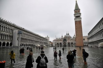 "People walk across the flooded St. Mark's square, with St. Mark's basilica and the Bell Tower in background, after an exceptional overnight ""Alta Acqua"" high tide water level, on November 13, 2019 in Venice. - Venice was hit by the highest tide in more than 50 years late November 12, with tourists wading through flooded streets to seek shelter as a fierce wind whipped up waves in St. Mark's Square. (Photo by Marco Bertorello / AFP)"