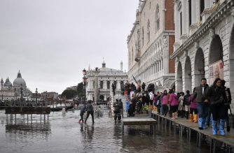 "Pedestrians walk on a footbridge across the flooded Riva degli Schiavoni embankment after an exceptional overnight ""Alta Acqua"" high tide water level, on November 13, 2019 in Venice. - Venice was hit by the highest tide in more than 50 years late November 12, with tourists wading through flooded streets to seek shelter as a fierce wind whipped up waves in St. Mark's Square. (Photo by Marco Bertorello / AFP)"