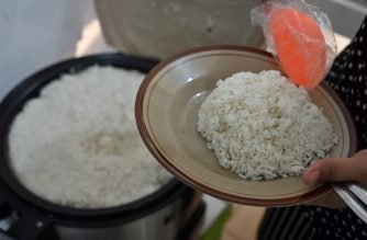 This picture taken on November 13, 2019 shows an Indonesian food vendor dishing out a plate of rice in Jakarta. - Rice, a staple food in more than 100 countries, is packed with fibre and key vitamins. But an unbalanced diet that relies too heavily on refined white rice has been linked to an increasing global prevalence of diabetes and insulin resistance as it raises blood sugar levels, according to experts. (Photo by ADEK BERRY / AFP) / TO GO WITH AFP STORY INDONESIA-HEALTH-FOOD-SOCIAL,FOCUS BY HAERIL HALIM