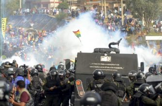 "Bolivian riot police clash with supporters of Bolivia's ex-President Evo Morales during a protest against the interim government, in Sacaba, Chapare province, Cochabamba department on November 15, 2019. - Bolivia's interim president Jeanine Anez said Friday that exiled ex-president Evo Morales would have to ""answer to justice"" over election irregularities and government corruption if he returns. (Photo by STR / AFP)"