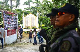 Police officers stand guard as relatives of the 58 people slain in the country's worst political massacre, visit the site of the massacre, in Ampatuan, Maguindanao province on the southern island of Mindanao on November 23, 2019. - Relatives of 58 people slain in the Philippines' worst political massacre held a tearful vigil on November 23 to mark a decade since the killings, voicing anger at the slow pace of justice. (Photo by Ferdinandh CABRERA / AFP)