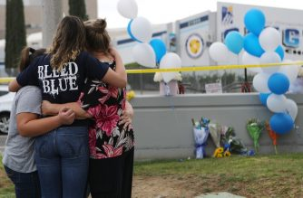 SANTA CLARITA, CALIFORNIA - NOVEMBER 15: A Saugus High School student (2nd L) is embraced as she visits a makeshift memorial in front of the school for victims of the shooting there on November 15, 2019 in Santa Clarita, California. The shooting left two students dead and others wounded while a suspect in the shooting is being treated at a local hospital for a gunshot wound to the head.   Mario Tama/Getty Images/AFP