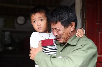 (FILE) Le Minh Tuan, father of 30-year old Le Van Ha, who was among the 39 people found dead in a truck in Britain, cries while holding Ha's son outside their house in Vietnam's Nghe An province on October 27, 2019. (Photo by NHAC NGUYEN / AFP)