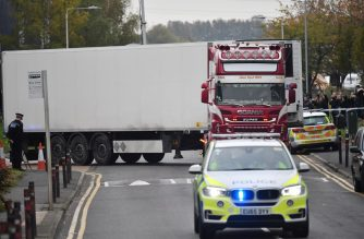 (FILE) Police officers drive away a lorry (C) in which 39 dead bodies were discovered sparking a murder investigation at Waterglade Industrial Park in Grays, east of London, on October 23, 2019. (Photo by Ben STANSALL / AFP)