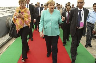 This handout photograph released by Delhi Metro Rail Corporation (DRMC) and taken on November 2, 2019, shows German Chancellor Angela Merkel (C) visiting DMRC's first roof top solar power plant installed in 2014 at Dwarka Sector – 21 metro station, in New Delhi. (Photo by Handout / Delhi Metro Rail Corporation (DRMC) / AFP)