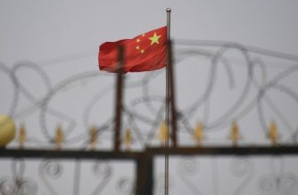 This photo taken on June 4, 2019 shows the Chinese flag behind razor wire at a housing compound in Yangisar, south of Kashgar, in China's western Xinjiang region. - A recurrence of the Urumqi riots which left nearly 200 people dead a decade ago is hard to imagine in today's Xinjiang, a Chinese region whose Uighur minority is straitjacketed by surveillance and mass detentions. A pervasive security apparatus has subdued the ethnic unrest that has long plagued the region. (Photo by GREG BAKER / AFP)