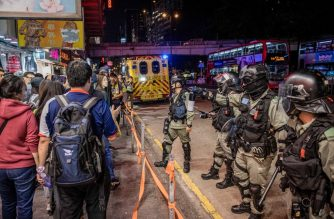 Riot police arrive to clear a barricade set up by protesters along Nathan road in Hong Kong on December 1, 2019. - Police fired tear gas and pepper spray in Hong Kong on December 1 as tens of thousands of black-clad protesters flooded into the streets, a week after pro-democracy candidates scored a landslide local election victory. (Photo by NICOLAS ASFOURI / AFP)