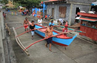 Residents carry to safety a wooden boat in Legaspi City, Albay province, south of Manila on December 2, 2019, as they prepare for Typhoon Kammuri. - The Philippines was braced for powerful Typhoon Kammuri as the storm churned closer, forcing evacuations and threatening plans for the Southeast Asian Games events near the capital Manila. (Photo by RAZVALE SAYAT / AFP)