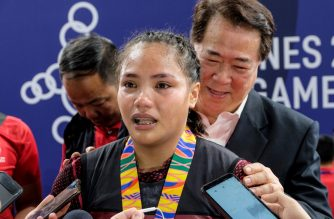Kristel Macrohon from the Philippines speaks to the media after winning the gold medal in the women's 71-kg weightlifting category at the SEA Games (Southeast Asian Games) in Manila on December 4, 2019. - Philippines weightlifter Kristel Macrohon claimed a tearful Southeast Asian Games gold medal as the regional Olympics got back into full swing on December 4, a day after being battered by a deadly typhoon. (Photo by James EDGAR / AFP)