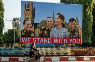 "(FILES) In this file photograph taken on November 28, 2019, a woman on motorcycle rides past a huge billboard depicting Myanmar State Counsellor Aung San Su Kyi with the three military ministers: L/R: border affairs minister Lieutenant General Ye Aung, defence minister Lieutenant General Sein Win and home affairs minister Lieutenant General Kyaw Swe with the background showing the building of the International Court of Justice in The Hague, displayed along a main road in Hpa-an, Karen State. - Former democracy icon Aung San Suu Kyi is set to make legal history when she defends Myanmar in The Hague on December 11, 2019, against charges of genocide targeting the Buddhist state's minority Rohingya Muslims. The tiny west African state of Gambia, acting on behalf of the 57-nation Organisation of Islamic Cooperation, will ask the International Court of Justice to take emergency measures to halt Myanmar's ""ongoing genocidal actions"". (Photo by - / AFP)"