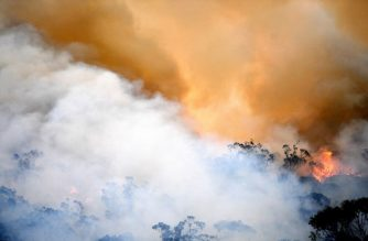 FILES: Smoke and flames from a back burn, conducted to secure residential areas from encroaching bushfires, are seen at the Spencer area in Central Coast, some 90-110 kilometres north of Sydney on December 9, 2019. - Australia is experiencing a horrific start to its fire season, which scientists say began earlier and is more extreme this year due to a prolonged drought and the effects of climate change. (Photo by SAEED KHAN / AFP)