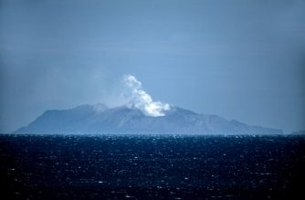 "Steam rises from the White Island volcano in Whakatane on December 10, 2019, after a volcanic eruption the day before. - New Zealand's Prime Minister Jacinda Ardern expressed ""unfathomable grief"" on December 10 after a volcanic eruption on a popular tourist island that is thought to have claimed 13 lives. (Photo by Marty MELVILLE / AFP)"