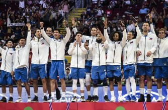 Players of the Philippines celebrate on the podium after winning gold medal in the men's final basketball event at the SEA Games (South East Asian Games) in Manila on December 10, 2019. (Photo by Sherwin Vardeleon / AFP)