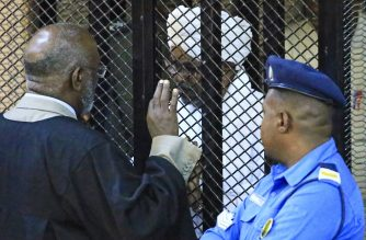 """Sudan's deposed military president Omar al-Bashir sits in a defendant's cage during his corruption trial at a court in Khartoum on December 14, 2019. - A Sudanese court  ordered former president Omar al-Bashir to be detained for two years in a correctional centre for corruption in one of several cases against the ousted autocrat. Bashir, who was toppled by the army in April after months of mass demonstrations, was convicted of graft and """"possession of foreign currency"""", judge Al Sadiq Abdelrahman said. (Photo by - / AFP)"""