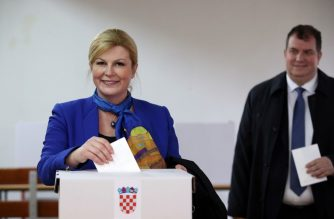 Croatian President Kolinda Grabar-Kitarovic (L) and her husband Jakov Kitarovic cast their ballot at a polling station during the Presidential elections on December 22, 2019 in Zagreb. - Croatia went to the polls for a presidential vote on Sunday that could weaken the ruling conservatives just as the country takes the helm of the European Union's rotating presidency. (Photo by Damir SENCAR / AFP)