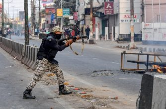 A security personnel fires tear gas during a curfew in Guwahati on December 12, 2019, following protests over the government's Citizenship Amendment Bill (CAB).  (Photo by Biju BORO / AFP)