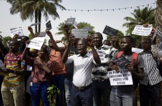 """Malian students and teachers hold signs reading """"A people without education is a people without a future"""" (bottom R) and """"Public school, private school, education remains a right for all"""" (top R) as they protest against the school strike which has been ongoing for one month and a half, on March 14, 2019 in Bamako. (Photo by MICHELE CATTANI / AFP)"""