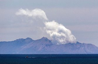 Steam rises from the White Island volcano following the December 9 volcanic eruption, in Whakatane on December 11, 2019. - The smouldering New Zealand volcano that killed at least six people is still too dangerous for emergency teams to recover bodies from, police said on December 11, warning that many tourists who escaped the island were so badly burned they were not yet out of danger. (Photo by Marty MELVILLE / AFP)