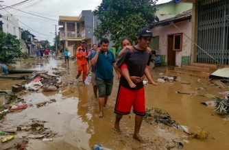 People walk through a muddy street at a housing complex in Bekasi, West Java on January 2, 2020, after flooding triggered by heavy rain hit the area. - The death toll from floods that hit Indonesia's capital region jumped to 18, authorities said on January 2, as torrential rains on New Year's Eve caused landslides and left vast swathes of the megalopolis submerged. (Photo by BAGUS SARAGIH / AFP)